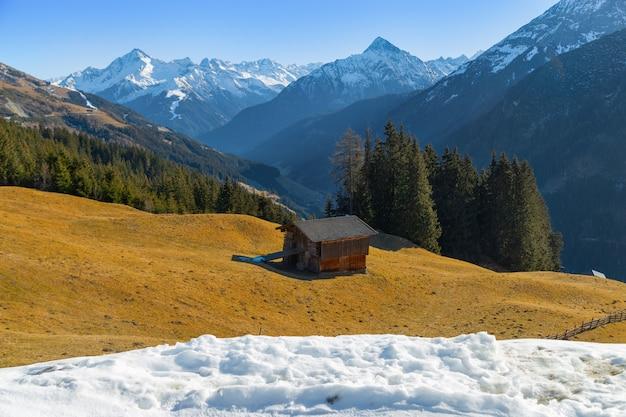 Paisagem montanhosa paisagem de inverno linda. as encostas dos alpes com a grama amarela. os topos das montanhas mais altas à distância.