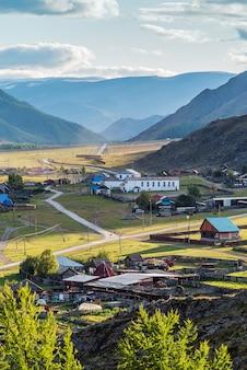 Paisagem montanhosa rural de outono com uma aldeia aldeia de altai da montanha russa de bichiktuboom