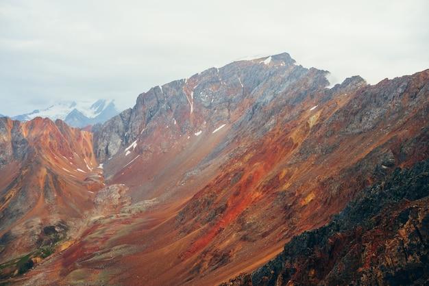 Paisagem multicolor vívida ao cume da grande montanha rochosa. close-up áspero da parede das montanhas gigantes. rochas e pedras vermelhas do amarelo alaranjado. belas paisagens das montanhas rochosas coloridas. cordilheira multicolorida.