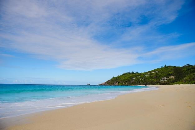 Paisagem natural com areia, mar e colina verde