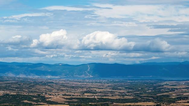 Paisagem natural da grécia, campos verdes, colinas verdes visíveis à distância, tempo nublado