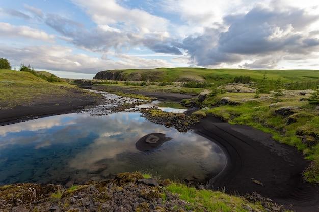 Paisagem natural de verão com areia preta na margem de um rio e nuvens no céu, islândia, europa