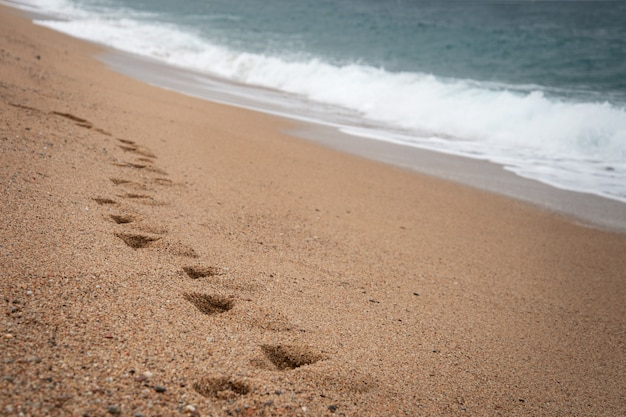 Paisagem natural marinha. ondas do mar lavam pegadas na areia