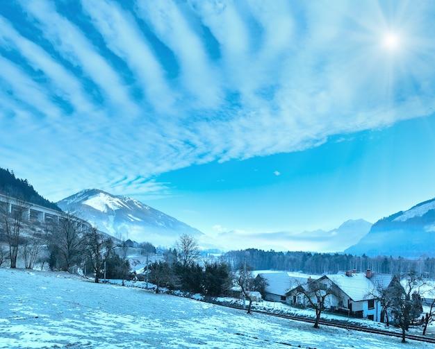 Paisagem nebulosa da vila ensolarada da montanha do inverno (áustria).