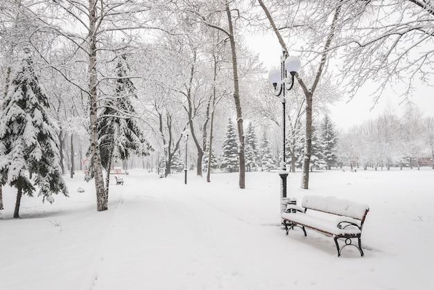 Paisagem nevada com bancos no parque da cidade de inverno