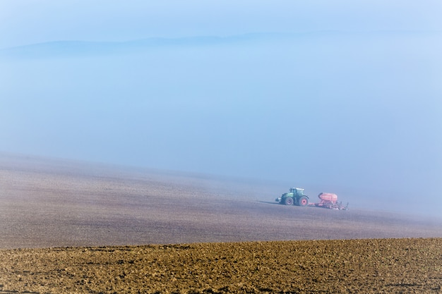 Paisagem nevoenta enevoada bonita do outono com o trator de trabalho em moravia sul, república checa.