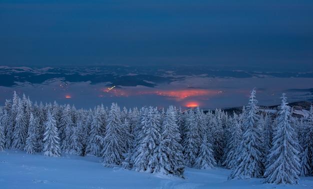 Paisagem no meio da noite. vista sobre a cidade pequena da montanha na noite no inverno.