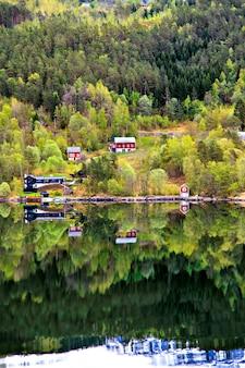 Paisagem norueguesa: aldeia, montanha e mar