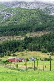 Paisagem norueguesa com casa de parede pintada de vermelho