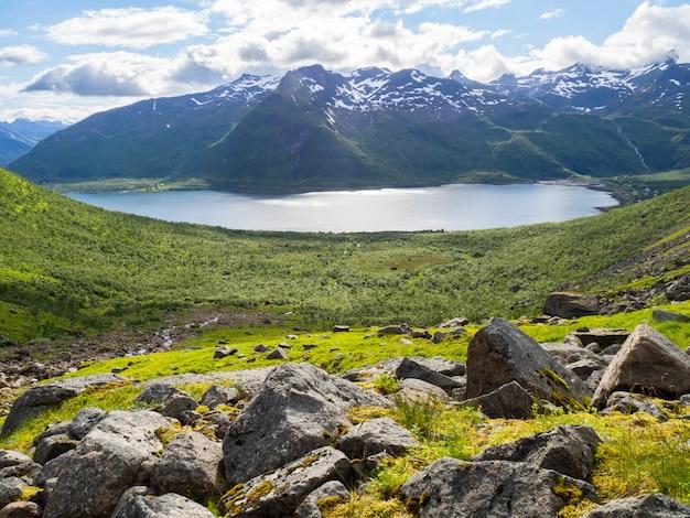 Paisagem norueguesa com vale verde entre montanhas com picos de neve.