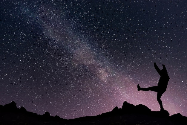Paisagem noturna com a via láctea no céu estrelado e a garota feliz no topo da montanha.
