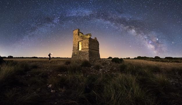 Paisagem noturna com a via láctea sobre um antigo castelo