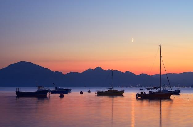 Paisagem noturna com barcos e iates no mar