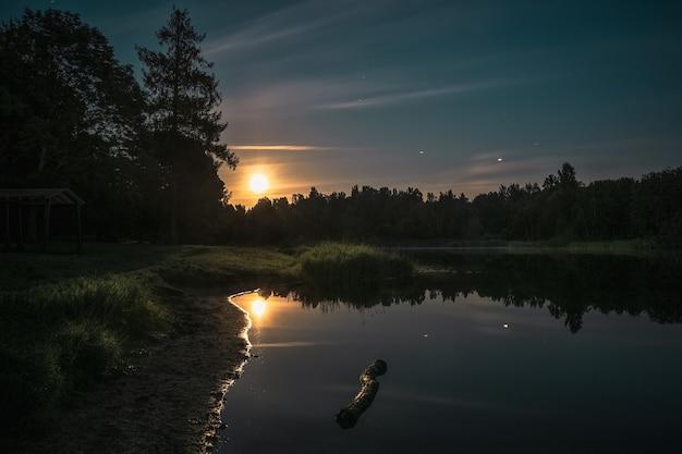 Paisagem noturna com o reflexo da lua no lago.