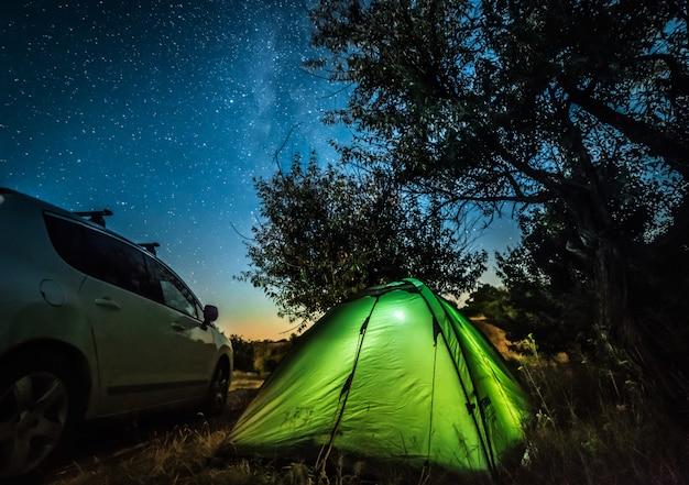 Paisagem noturna com tenda e carro