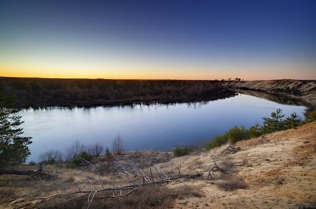 Paisagem noturna com um rio, ao pôr do sol