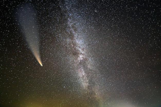 Paisagem noturna da via láctea com céu coberto de estrelas e cometa c / 2020 f3 (neowise) com cauda clara no céu escuro