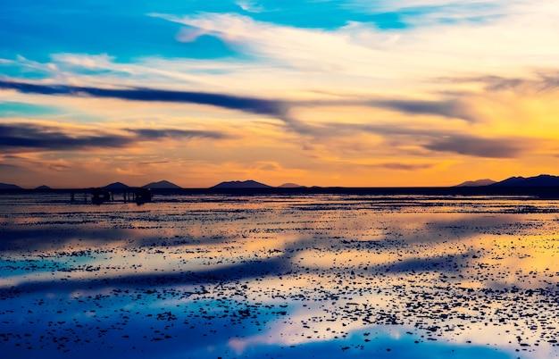 Paisagem noturna de salar de uyuni no pôr do sol com reflexo na superfície