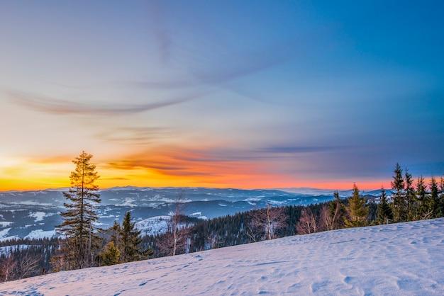Paisagem pacífica no vale da montanha com floresta de abetos e montes de neve no contexto do pôr do sol e céu azul com nuvens.