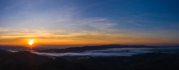 Paisagem panorâmica a luz do sol com céu azul na montanha na névoa da manhã