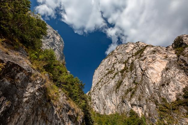 Paisagem panorâmica alpina de montanha cênica, rochas cinzas, céu azul