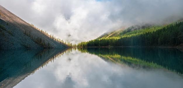 Paisagem panorâmica de manhã com densa névoa sobre o lago. reflexo de árvores coníferas em águas calmas e brilhantes. paisagem alpina tranquila no início da manhã. cenário atmosférico fantasmagórico.