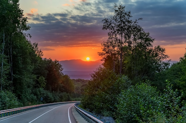 Paisagem pitoresca com pôr do sol e estrada estreita nas montanhas de verão