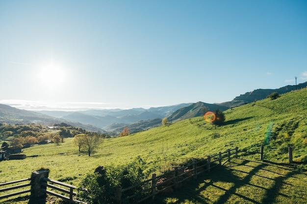 Paisagem pitoresca da encosta gramada do cume da montanha contra o céu azul sem nuvens no dia ensolarado
