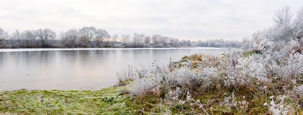 Paisagem pitoresca de inverno com árvores cobertas de neve e arbustos à beira do rio em uma manhã de inverno em tons frios de inverno