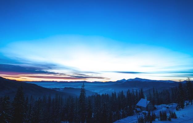 Paisagem pitoresca de montanha à noite em uma casa de férias no meio de encostas e árvores altas