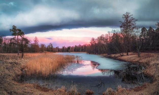 Paisagem pitoresca de outono com um lago. noite paisagem do sol de primavera com um remanso e gelo no lago. gatchina. rússia.