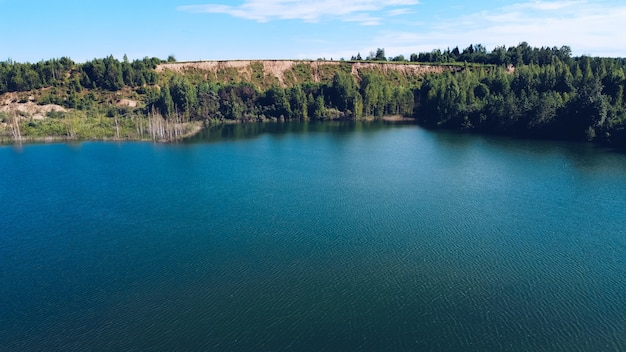 Paisagem pitoresca do verão do lago azul para férias ao ar livre. colina com uma vegetação luxuriante atrás do meio do lago. distrito de volokolamsk da região de moscou. praia sychevo, rússia