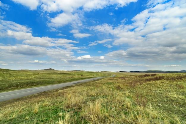 Paisagem pitoresca estepe. céu azul, grama, estrada. parque natural nacional de burabay, na república do cazaquistão. tempo de primavera. viaje para a ásia central. maio, 2019.