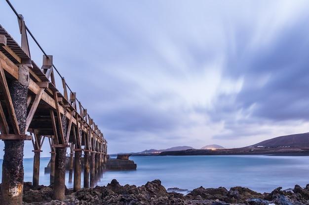 Paisagem por do sol com ponte na praia, whit céu nublado nas ilhas canárias lanzarote