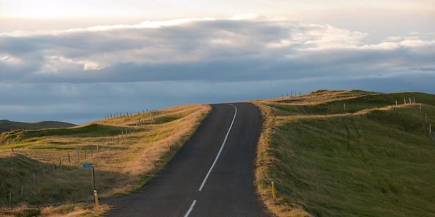 Paisagem, rodovia desaparecendo no horizonte através de terras agrícolas, em um dia nublado