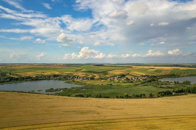 Paisagem rural aérea com campos de agricultura remendados amarelo e céu azul com nuvens brancas.