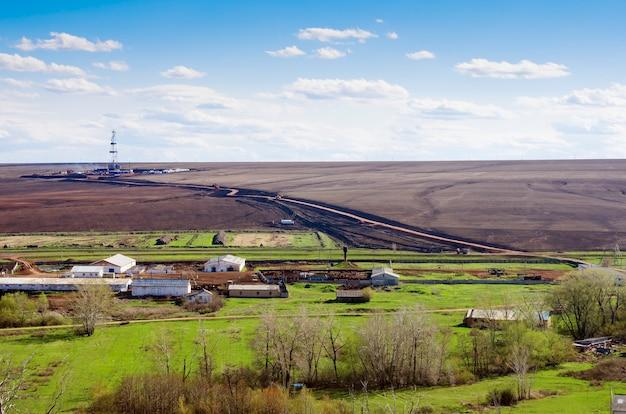 Paisagem rural com fazenda de criação de gado e torre de perfuração vista de cima