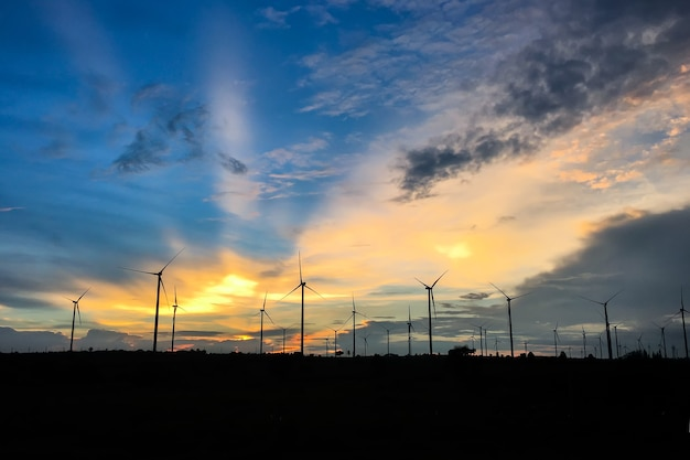 Paisagem rural com turbinas eólicas no campo agrícola ao pôr do sol