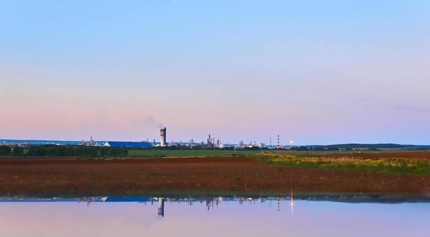 Paisagem rural com uma fábrica de produtos químicos no horizonte refletida na água.
