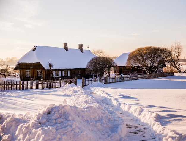 Paisagem rural do inverno: casas na neve