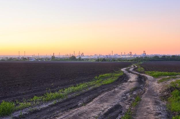 Paisagem rural noturna com campos arados, estrada de terra e uma enorme refinaria de petróleo no horizonte