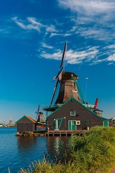 Paisagem rural pitoresca com moinhos de vento em zaanse schans perto do rio, holanda, holanda