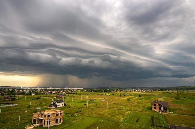 Paisagem temperamental com nuvens escuras de tempestade e chuva forte caindo sobre edifícios distantes da cidade no verão