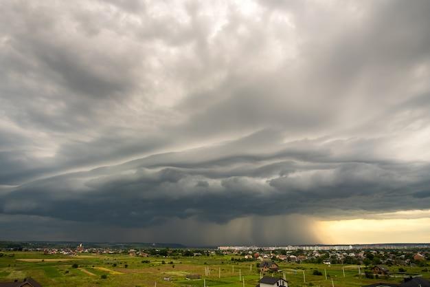 Paisagem temperamental com nuvens escuras e tempestuosas, com forte chuva torrencial sobre edifícios distantes da cidade