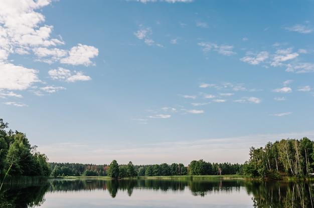 Paisagem tranquila em um lago, com o céu azul vibrante, as nuvens brancas e as árvores refletidas simetricamente na água azul limpa.