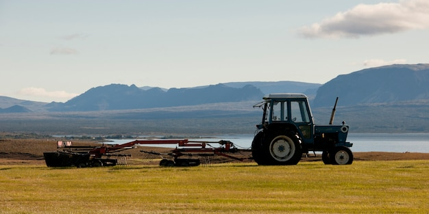 Paisagem, trator, puxando máquinas agrícolas antes da montanha acidentada