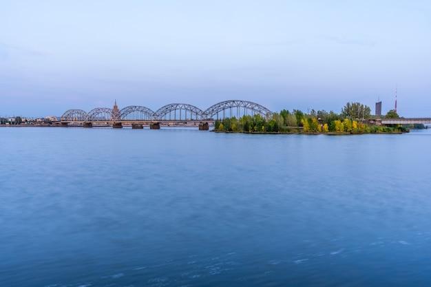 Paisagem urbana com a ponte ferroviária em riga, letônia, na hora azul sobre o rio daugava