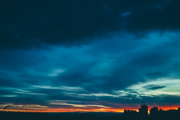 Paisagem urbana com maravilhoso amanhecer vívido lanxess. incrível céu nublado multicolorido dramático acima silhuetas escuras dos edifícios da cidade. atmosférico do nascer do sol em tempo nublado. copyspace.