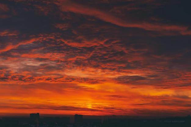 Paisagem urbana com o amanhecer de vampiro de sangue ardente. incrível quente céu nublado dramático acima silhuetas escuras dos edifícios da cidade. luz do sol laranja. fundo atmosférico do nascer do sol em tempo nublado. copie o espaço.