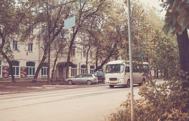 Paisagem urbana com ônibus velho na estrada. retro tonificado.